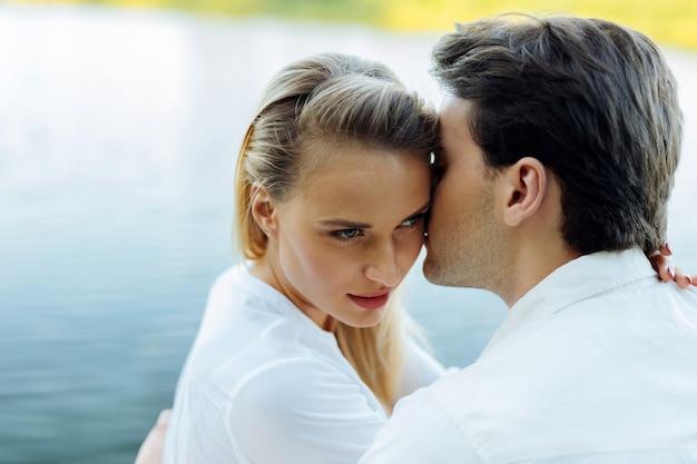 幸せなカップル。川の近くに座っている間、彼女の夫にキスされている美しい若い女性