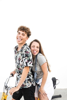 Happy couple on bicycle against white wall teasing