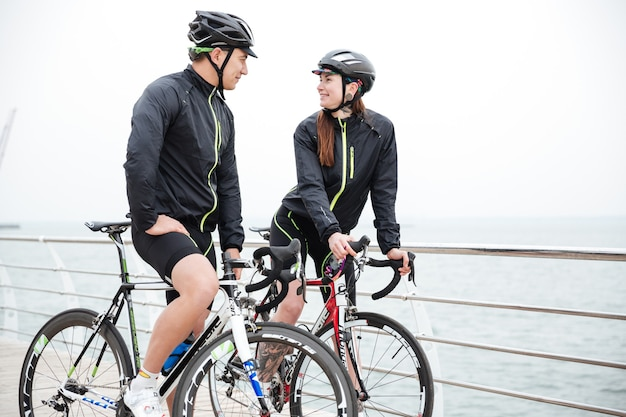 Happy couple on bicycle resting and flirting near sea