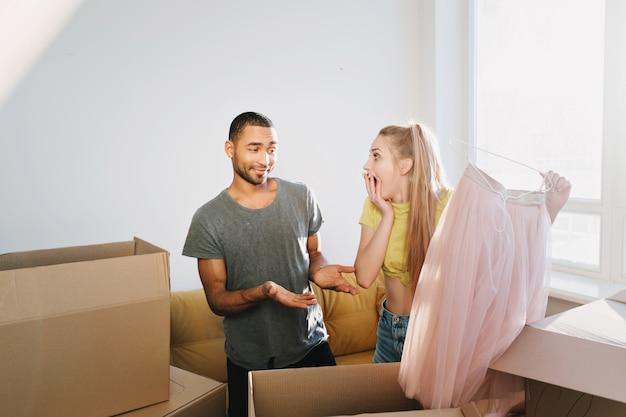 Una coppia felice ha comprato casa, la famiglia si è trasferita in un nuovo appartamento, ha inaugurato la casa, ha disimballato le scatole. donna trovata presente, marito sorpreso moglie, gonna rosa in regalo. uomo che indossa la maglietta grigia, ragazza gialla in alto.