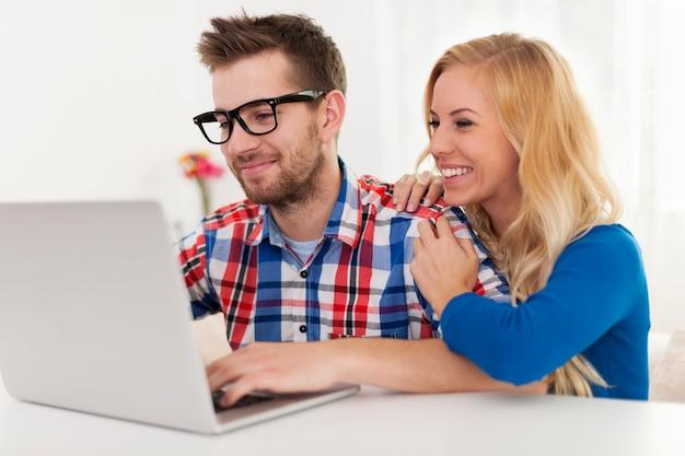 Coppie felici che passano in rassegna qualcosa sul computer portatile