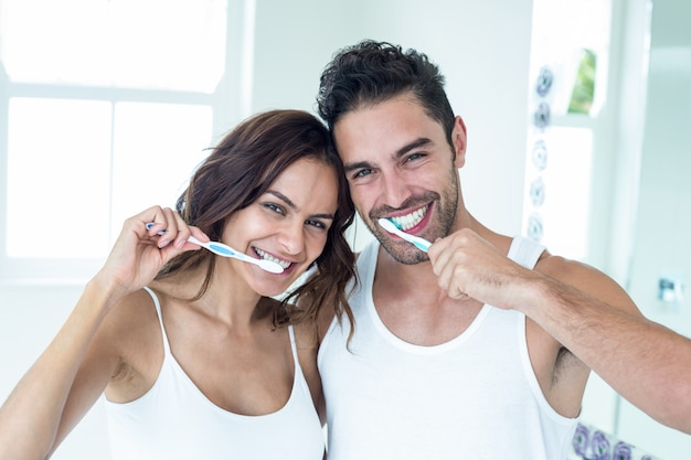 Happy couple brushing teeth in bathroom