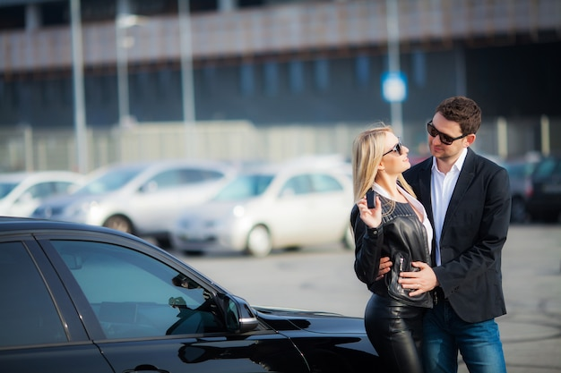 Happy couple buy new modern black car