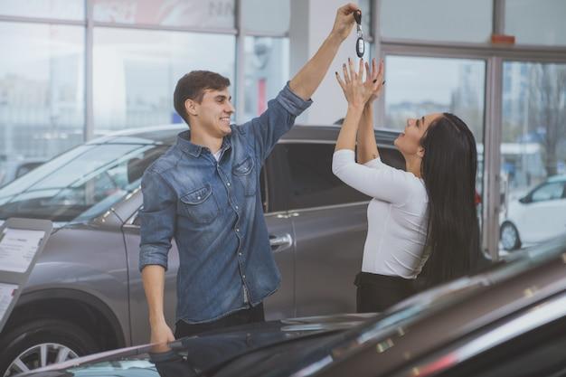 Happy couple buying new car at dealership salon