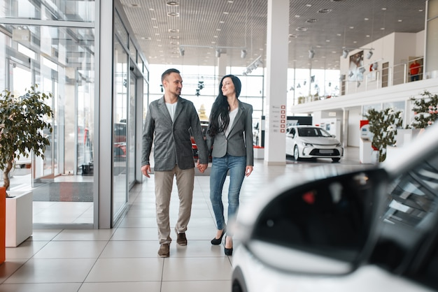Happy couple buying new car in showroom