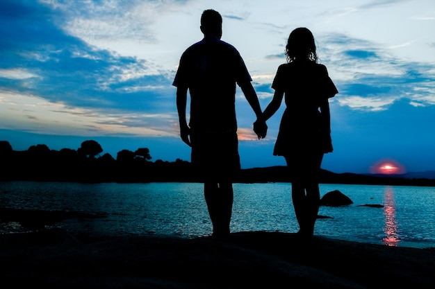 Happy couple by the sea on nature silhouette