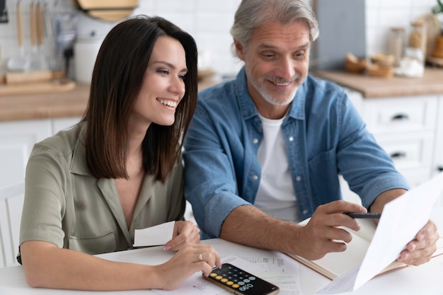 Happy couple calculating bills at home, received debt mortgage notification, checking financial documents
