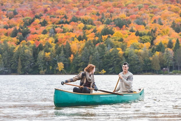 Happy couple canoeing in a lake in canada