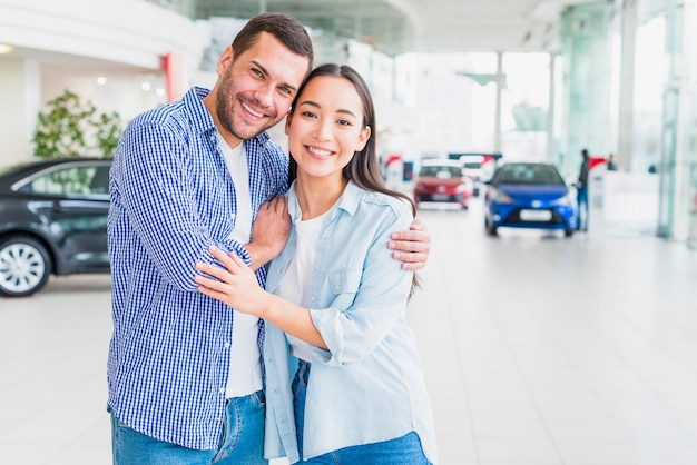 Happy couple at car dealership