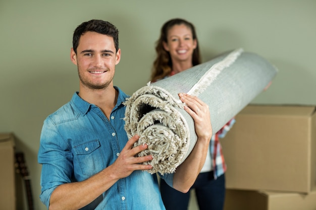 Happy couple carrying rolled up rug in their new house