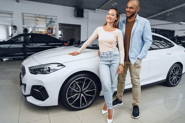 Happy couple of caucasian woman and african american man standing near their new luxury car inside car salon