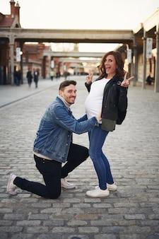 행복한 커플은 임신을 맞는다. 어머니는 손으로 승리 기호를 만든다. 남편은 그녀의 배를 잡고 무릎을 꿇고 있습니다.
