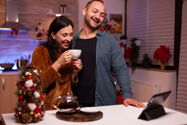 Happy couple celebrating christmas holiday with remote friends during online videocall