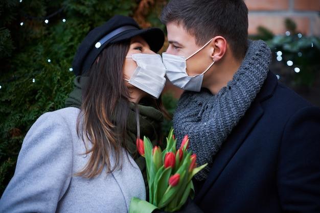 街でのcovid-19パンデミックの間にマスクでバレンタインデーを祝う幸せなカップル
