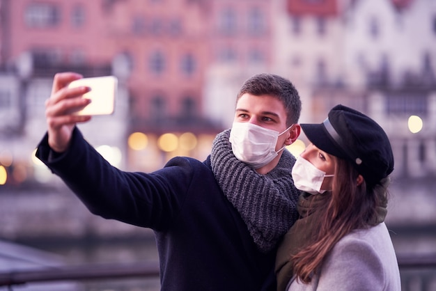 Happy couple celebrating valentines day in masks during covid-19 pandemic in the city