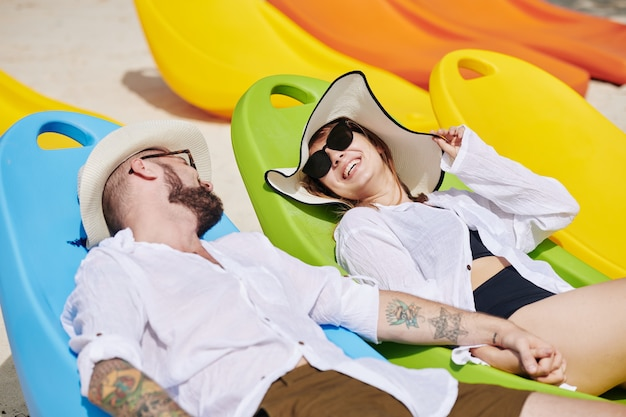 Happy couple on chaise-lounges
