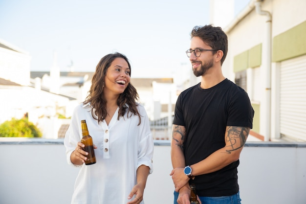 幸せなカップルのチャット、笑い、ビールを飲む