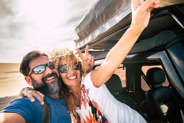 幸せなカップルは陽気で、車の旅の間に関係と幸せと一緒に抱き合ってセルフィーの絵のスタイルで笑顔-バックゴーンドの砂漠と空-夏休みの楽しい人々