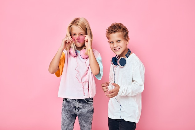 Happy couple child entertainment headphones playing pink color background