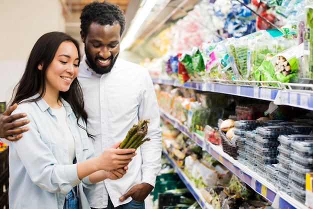 Happy couple choosing asparagus in grocery store