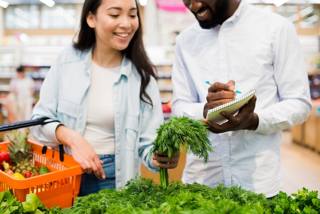 Happy couple choosing greenery in grocery store