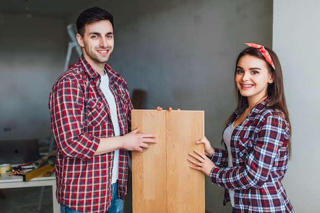 新しいアパートのためのラミネートフローリングを選ぶ幸せなカップル