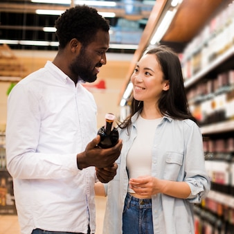 Happy couple choosing wine in grocery store