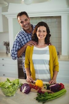 幸せなカップルが台所で野菜を刻んで