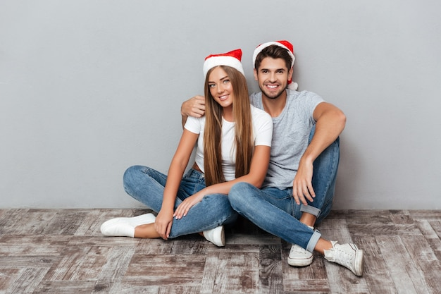 Happy couple in christmas hats are cuddling