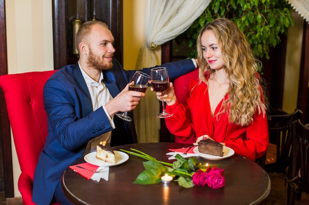 Happy couple clanging glasses at table in restaurant