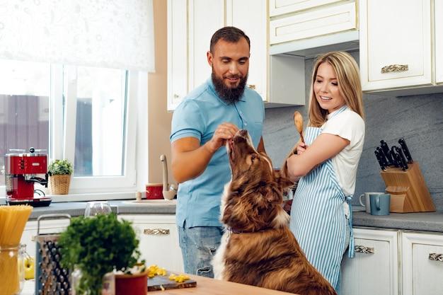 幸せなカップルが彼らの犬と一緒にキッチンで料理