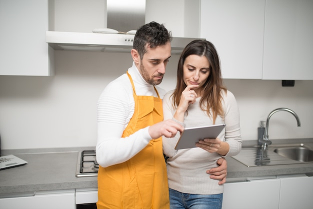 Happy couple cooking in their kitchen