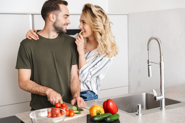 Счастливая пара готовит вместе, стоя на кухне, нарезая овощи на борту, обнимая