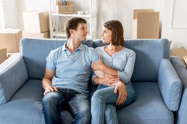Coppia felice sul divano durante l'imballaggio per cambiare casa