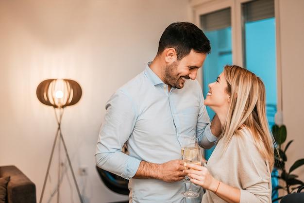 Happy couple cuddling while enjoying white wine at home.
