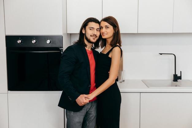 幸せなカップルがかわいいキッチンでお互いに触れます。高品質の写真