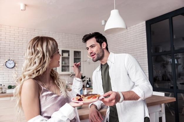 幸せなカップル。白いシャツを着た黒髪のひげを生やした男と彼の妻は一緒に朝食を楽しんでいます