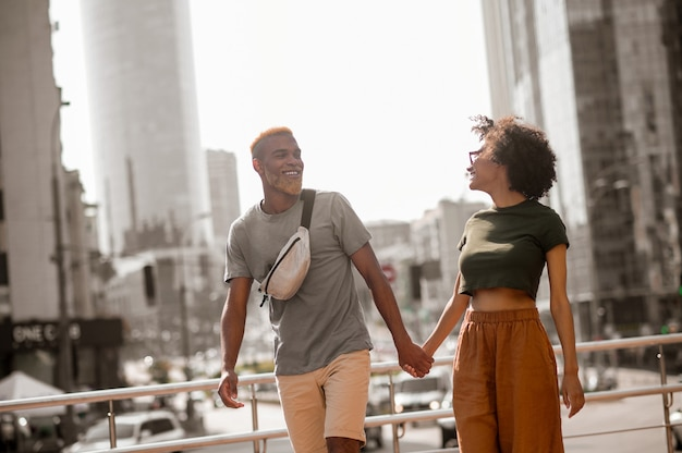 幸せなカップル。通りを歩いて手をつないでいる浅黒い肌のカップル