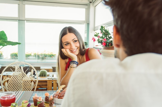 Happy couple dating at a restaurant. woman in love having a conversation with her boyfriend