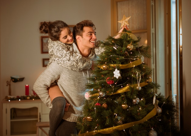 Happy couple decorating christmas tree with star
