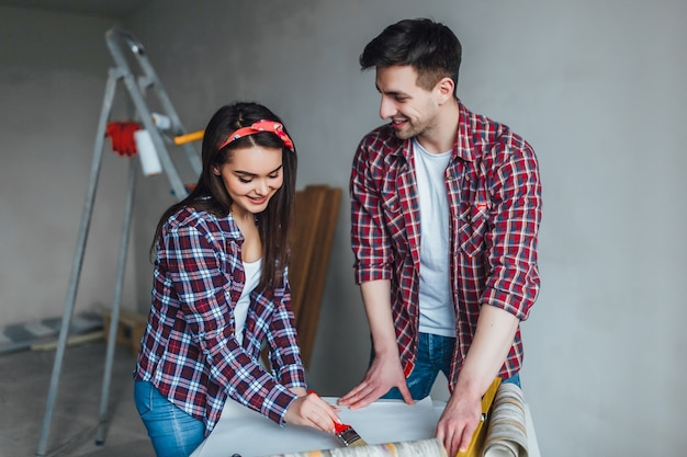 Счастливая пара проектирует свой новый дом, они вместе проверяют проект дома и делают ремонт дома