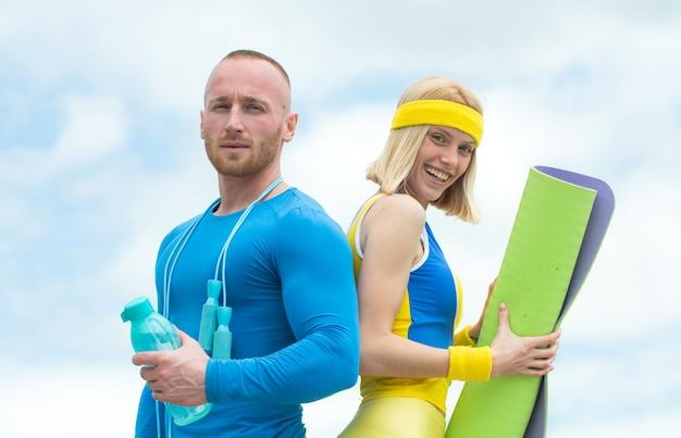 自然の中で屋外で運動をしている幸せなカップルは、朝のトレーニングでアスリートをクローズアップ強力なハンサム...