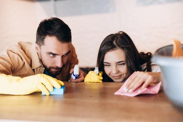 自宅のモダンなキッチンで家の掃除をしている幸せなカップル
