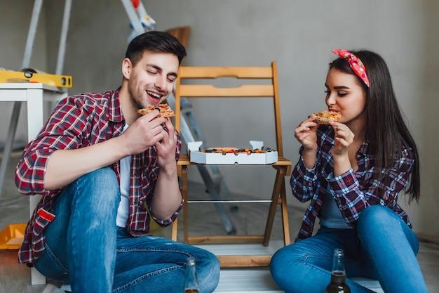 Coppia felice che fa le riparazioni a casa e ha un momento romantico per mangiare la pizza