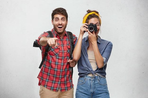 Счастливая пара, одетая небрежно позирует