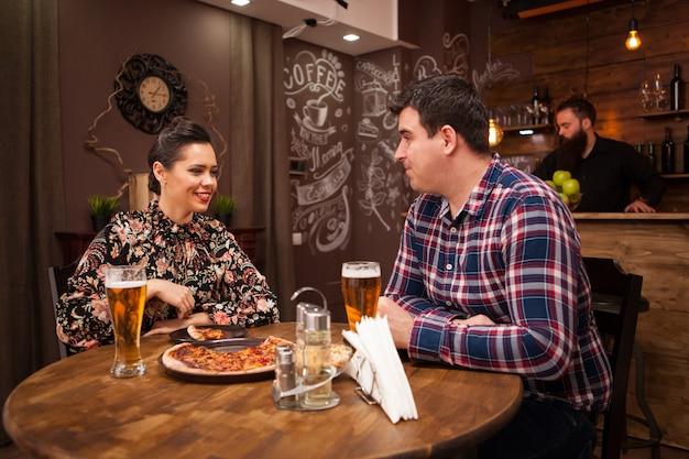 Coppia felice che beve birra e mangia pizza. tempo casuale.