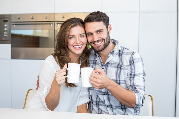 Happy couple drinking coffee by table