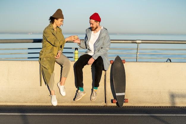 롱보드가 가까이 있는 트렌디한 거리 패션 옷을 입은 다리 브로드워크에 앉아 야외에서 뜨거운 차를 마시는 행복한 커플. 일몰에 스케이트보드를 탄 후 상쾌한 젊은 힙스터 남자와 여자