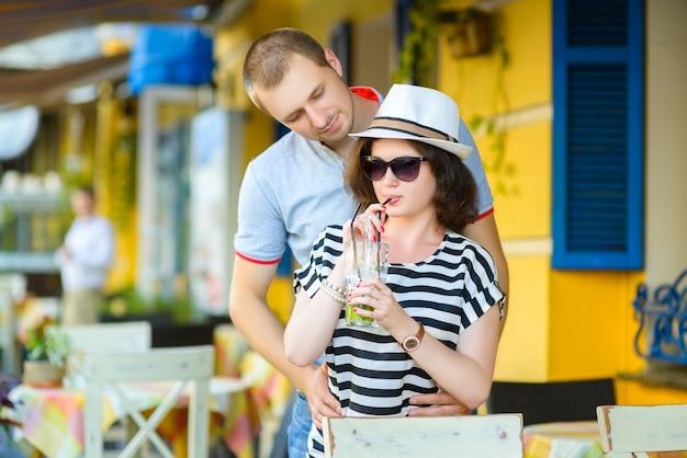 外のカフェでレモネードを飲んで幸せなカップル。