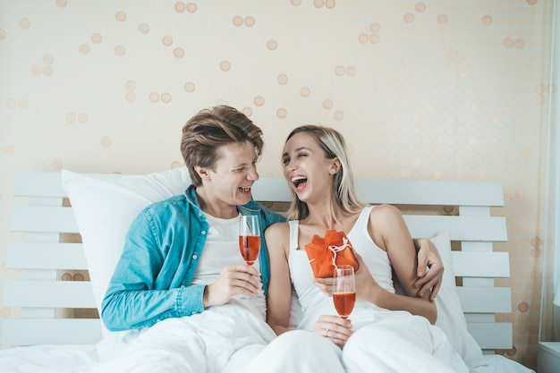 Happy couple drinking wine in the bedroom